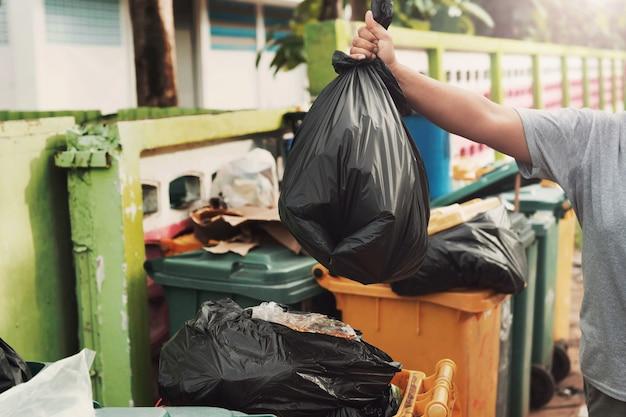 Frauenhand, die abfall in der schwarzen tasche hält, damit sie herein säubert, um wegzuwerfen