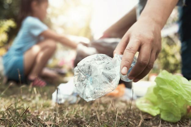 Frauenhand, die abfallflasche für das säubern am park aufhebt