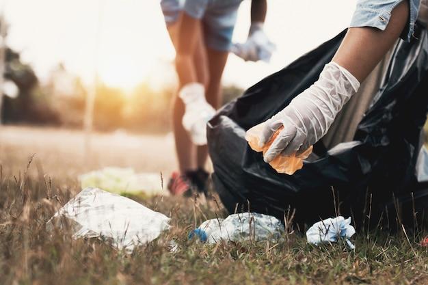Frauenhand, die abfallplastik für das säubern am park aufhebt