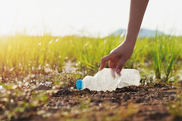 Frauenhand, die abfallplastik für das säubern in fluss aufhebt