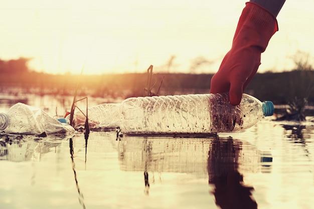Frauenhand, die abfallplastik für das säubern in fluss mit sonnenuntergang aufhebt