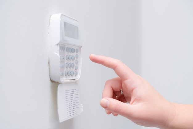 Frauenhand, die alarmsystempasswort einer wohnung, eines hauses oder eines geschäftsbüros eingibt.