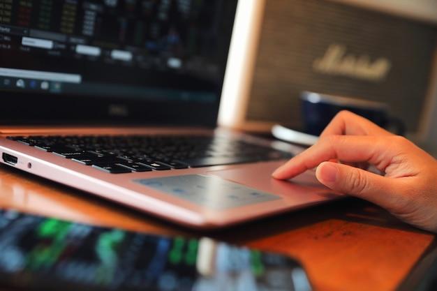 Frauenhand, die an der kaffeestubehand auf tastatur mit abschluss oben arbeitet