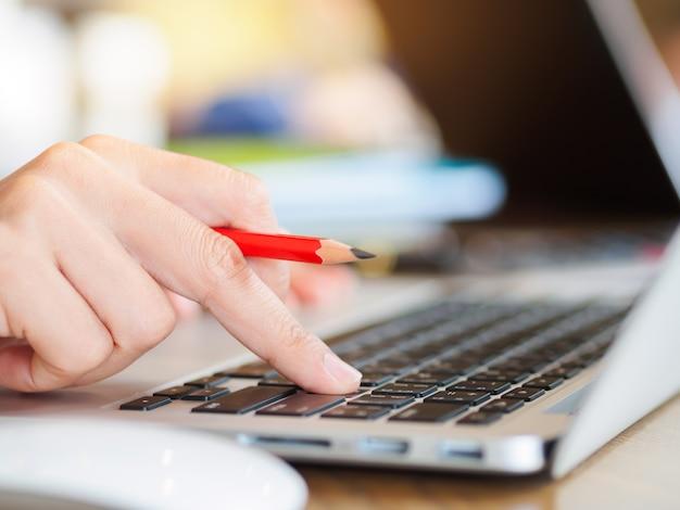 Frauenhand, die an ihrem laptop arbeitet. sozial-, technologie-konzept.