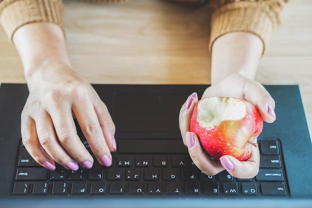 Frauenhand, die apfel am schreibtisch isst