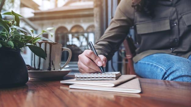 Frauenhand, die auf leeres notizbuch mit kaffeetasse auf holztisch schreibt