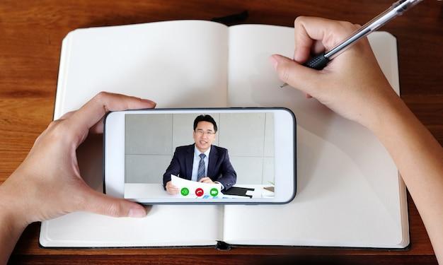 Frauenhand, die auf notizbuch schreibt, während handy für online-klasse verwendet wird