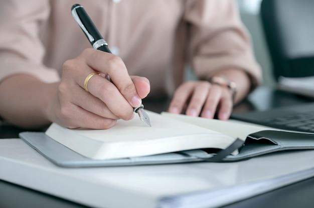 Frauenhand, die auf tagebuch mit stift schreibt