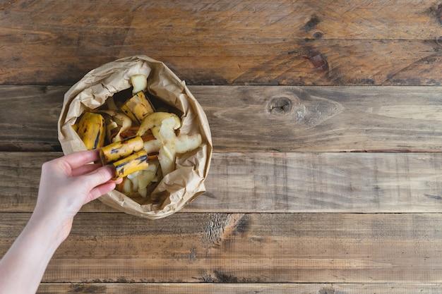 Frauenhand, die bananenschale in papiertüte auf hölzernem hintergrund ablegt.