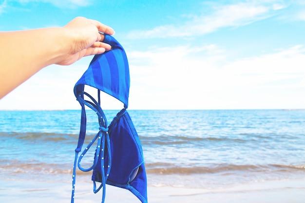 Frauenhand, die bikini mit meer und blauem himmel im hintergrund, glückliche ferien hält
