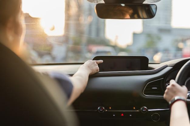 Frauenhand, die bildschirm in einem auto berührt, während ihr freund fährt.