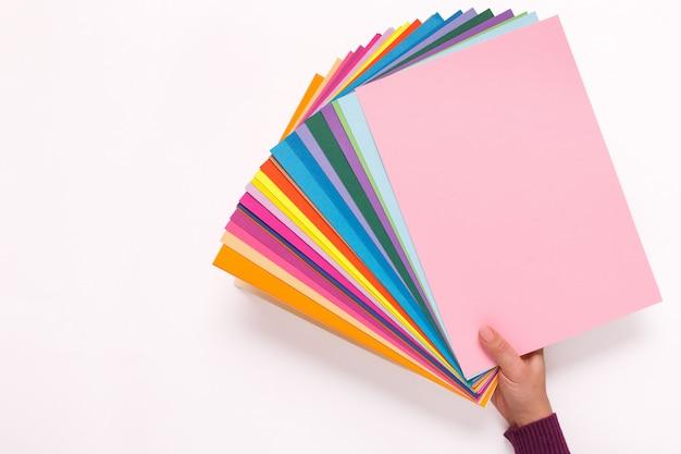 Frauenhand, die blätter des verschiedenfarbigen papiers hält.