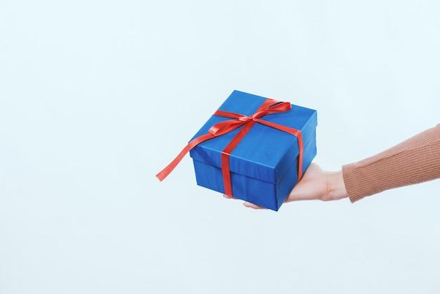 Frauenhand, die blaue geschenkbox über weißem hintergrund hält