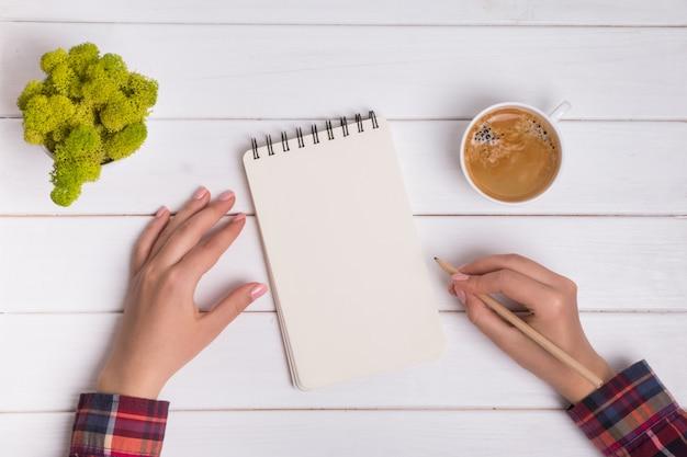 Frauenhand, die bleistift hält und in leeren notizblock schreiben wird