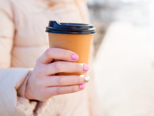 Frauenhand, die braune papierkaffeetasse im freien hält.