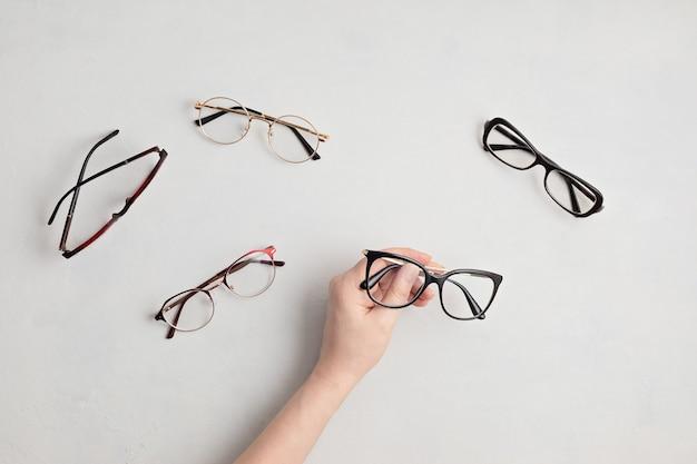 Frauenhand, die brillen hält. optischer laden, brillenauswahl, sehtest, sichtprüfung beim optiker, modeaccessoire-konzept. draufsicht, flach liegen