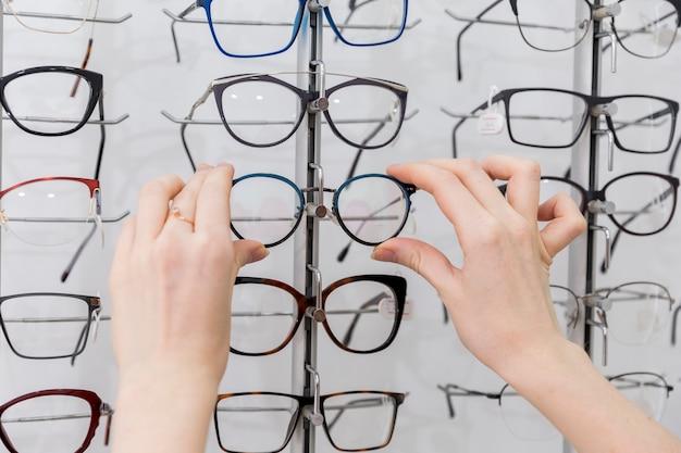 Frauenhand, die brillen im optikshop hält