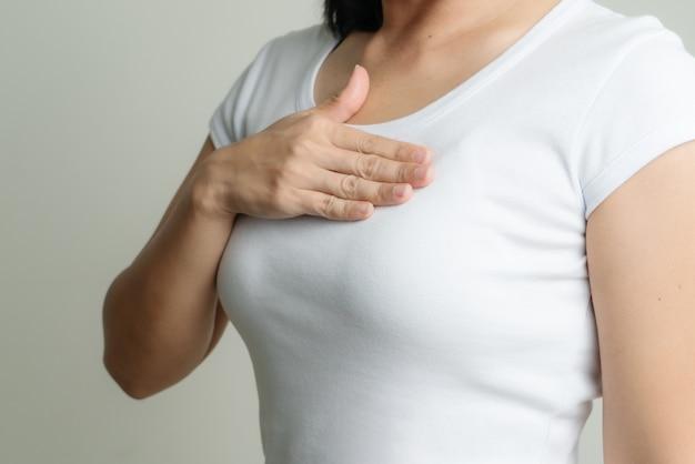 Frauenhand, die brust berührt, um brustkrebsursache zu unterstützen. konzept zur aufklärung über brustkrebs