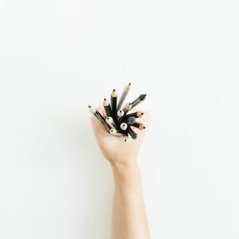 Frauenhand, die bündel von stiften auf weißer oberfläche hält
