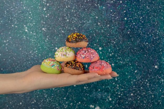 Frauenhand, die bunte süße donuts mit streuseln hält.