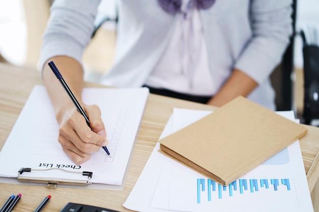 Frauenhand, die checklistenpapier, memo-planungskonzept schreibt. papierkram zum ausfüllen von geschäftsinformationen.