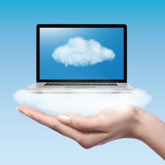 Frauenhand, die computer-laptop auf blauer oberfläche hält