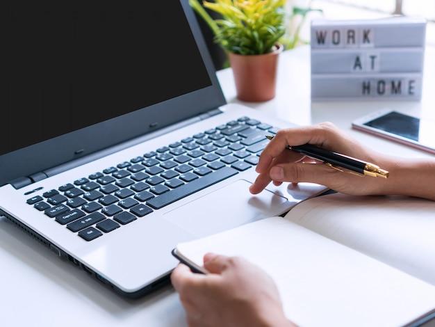 Frauenhand, die computer-laptop auf weißem schreibtisch mit tagebuch, smartphone und arbeit zu hause wort auf leuchtkasten verwendet. speicherplatz kopieren, nahaufnahme. quarantäne, neues normales home-office-konzept.