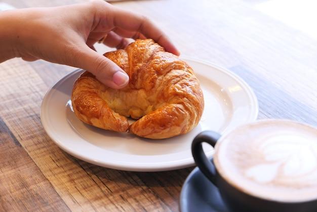 Frauenhand, die croissant auf holztisch hält.