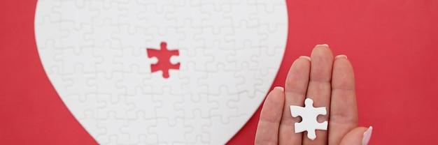 Frauenhand, die das letzte stück von den puzzles in form der herznahaufnahme hält. valentinstagkarten-konzept