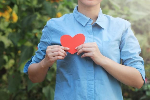 Frauenhand, die das liebessymbol auf der rechten brust für eine illustration der liebenden brustgesundheit hält