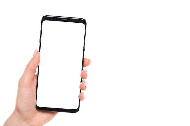 Frauenhand, die den leeren bildschirm des schwarzen smartphones mit modernem rahmenlosem design lokalisiert auf weißem hintergrund hält