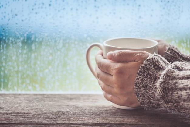 Frauenhand, die den tasse kaffee oder den tee am regnerischen tagesfensterhintergrund hält