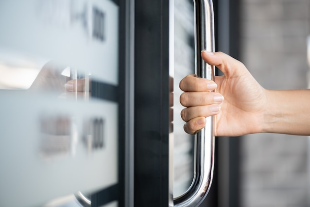 Frauenhand, die die türstange hält, um die tür mit glasreflexionshintergrund zu öffnen.