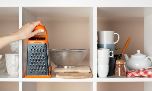 Frauenhand, die dishwarestücke vom regal in der küche nimmt