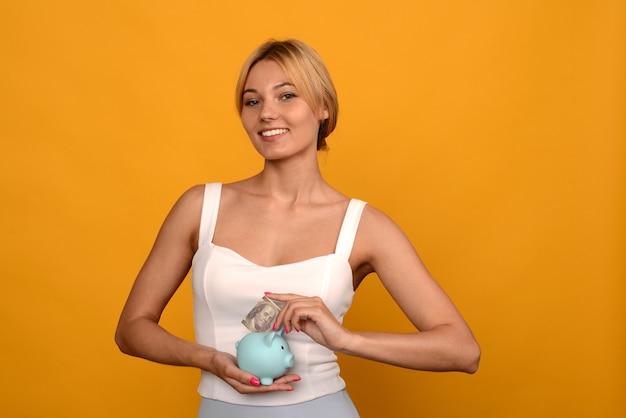 Frauenhand, die dollars in schweinchen setzt, um geld, reichtum und finanzkonzept zu sparen.