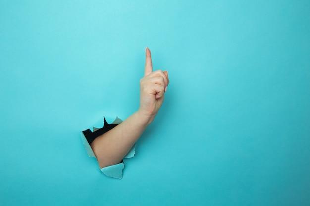 Frauenhand, die durch blaue papierwand mit fingerspitze nach oben bricht