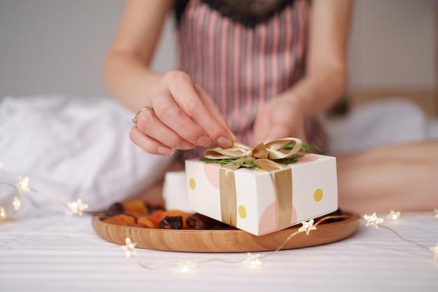 Frauenhand, die ein geschenk auspackt, während im bett mit lichtern auf den weißen laken sitzt