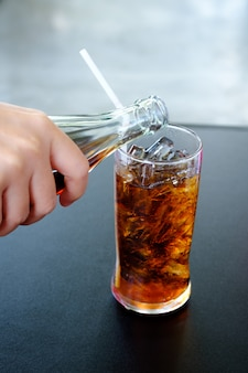 Frauenhand, die ein glas alkoholfreie getränke mit eis gibt
