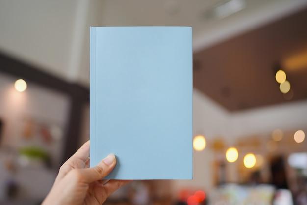Frauenhand, die ein hellblaues buch mit leerem einband zum einfügen von text auf unscharfem café-hintergrund hält