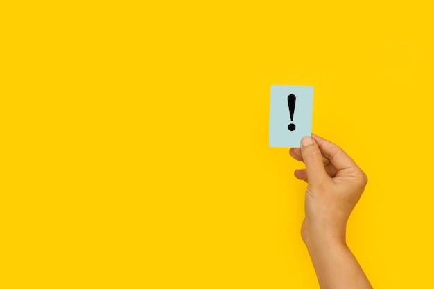 Frauenhand, die ein papier mit einem ausrufezeichen auf einem gelben hintergrund hält