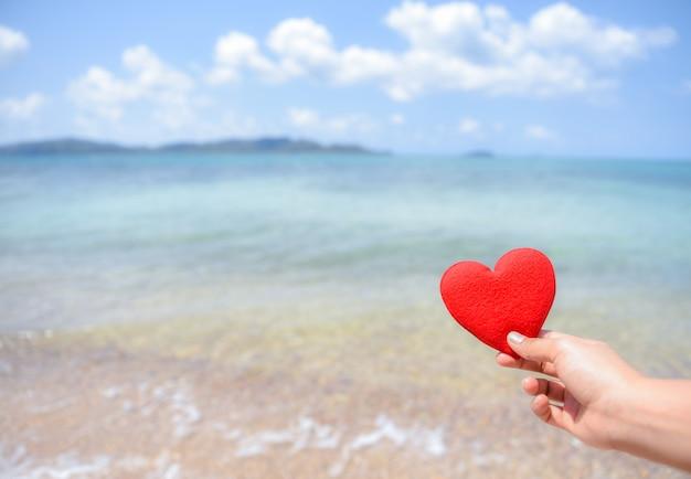 Frauenhand, die ein rotes herz auf dem strand mit unscharfem hintergrund des meeres und des blauen himmels hält. liebe konzept.