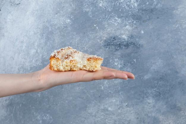 Frauenhand, die ein stück des köstlichen kuchens auf einem steintisch hält.