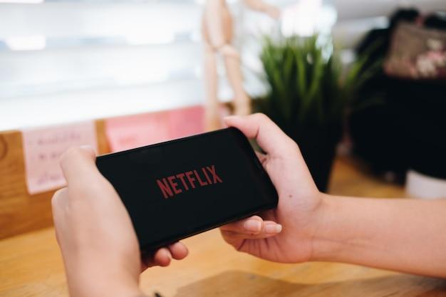 Frauenhand, die ein telefon mit einem globalen anbieter von streaming-filmen und fernsehserienlogo hält