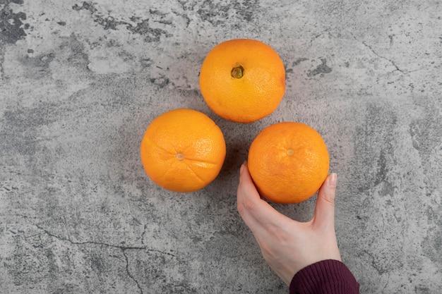Frauenhand, die eine frische orange frucht auf steintisch nimmt.