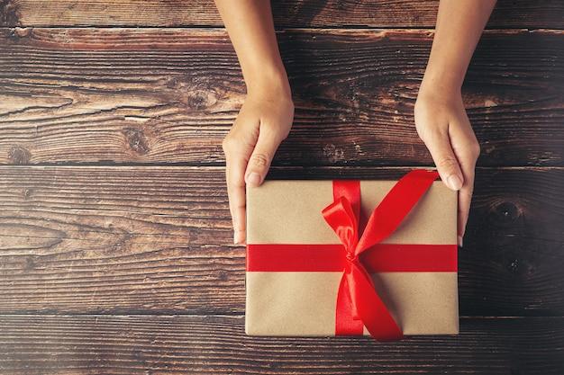 Frauenhand, die eine geschenkbox mit rotem band auf holzboden hält