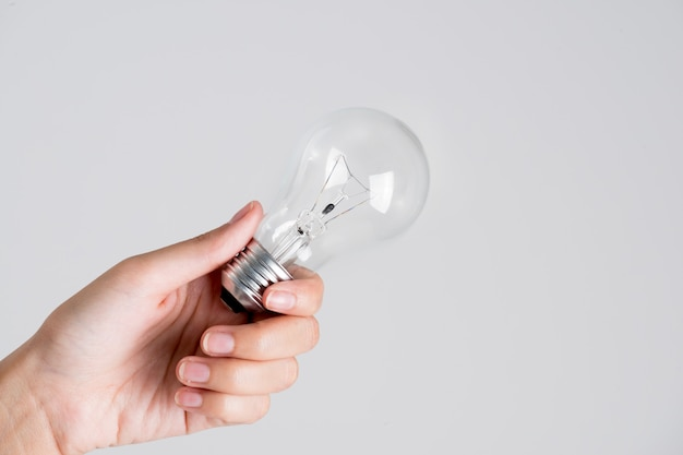 Frauenhand, die eine glühlampe auf weißem hintergrund gibt