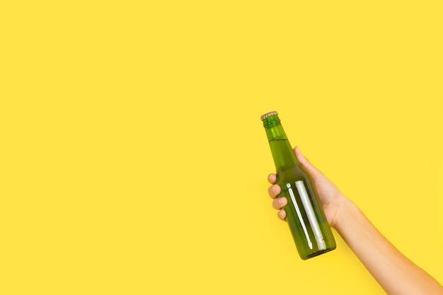 Frauenhand, die eine grüne flasche bier auf gelbem hintergrund mit kopienraum hält