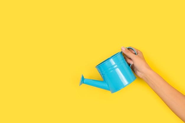 Frauenhand, die eine hellblaue gießkanne auf gelbem hintergrund mit kopienraum hält