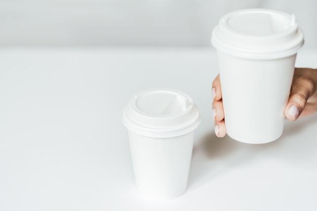 Frauenhand, die eine kaffeepapiertasse hält