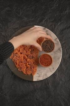 Frauenhand, die eine kleine hölzerne schüssel mit pfeffer auf schwarzem tisch hält